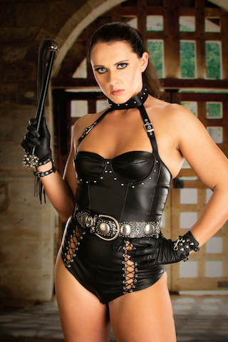 dominatrix sara in leather outfit holding whip, uk